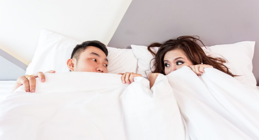 Couple Under A Bed Mattress